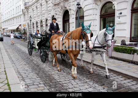 Horse drawn carriage with tourists in the streets of Vienna, Austria - Stock Photo