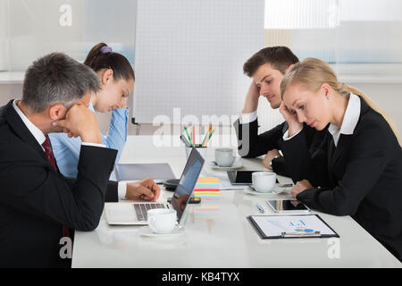 Team Of Unhappy Businesspeople Sitting In Business Meeting - Stock Photo