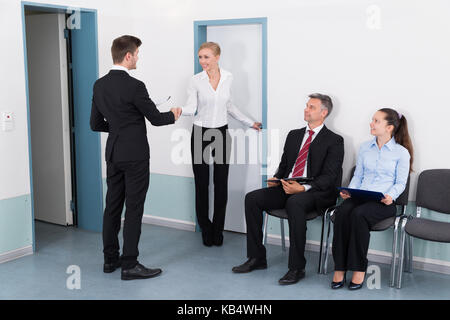 Businesswoman Shaking Hands With Man In Front Of People Waiting For Job Interview In Office - Stock Photo