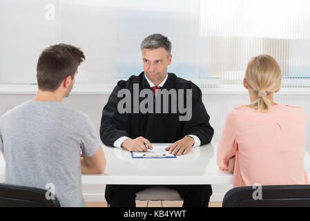 Mature Male Judge Sitting In Front Of Young Couple In Courtroom - Stock Photo