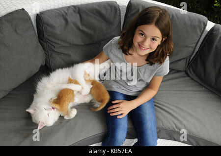 Girls in jeans and grey T-shirt beside nursing cat on grey sofa, looking into camera - Stock Photo