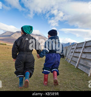 Children holding hands in the countryside at a horse gathering in Iceland.  Annual Horse Round Up-Laufskalarett, - Stock Photo