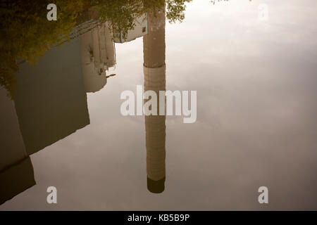 a smoking chimney on the water of a house in front of evening sky - Stock Photo