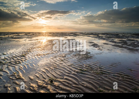 View of sandy beach and pools at low tide, at sunset, Reculver, Kent, England, United Kingdom, Europe - Stock Photo