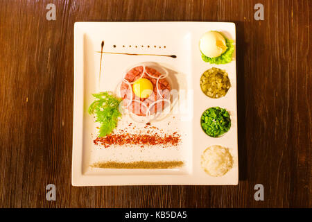 Tasty dish of raw meat, egg yolk, greens and spices placed on the white rectangular plate. The above view. - Stock Photo