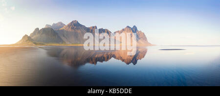 Panoramic view of Vestrahorn Mountain range reflecting in shallows of black volcanic beach, Stokksnes, South Iceland - Stock Photo