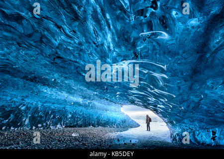 View from inside ice cave under the Vatnajokull Glacier with person for scale, near Jokulsarlon Lagoon, South Iceland - Stock Photo