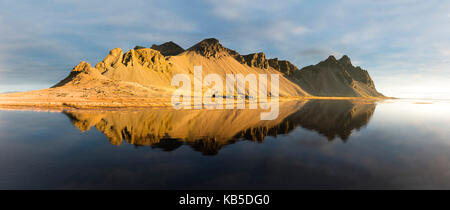 Panoramic view of mountains of Vestrahorn and perfect reflection in shallow water, soon after sunrise, Stokksnes, - Stock Photo
