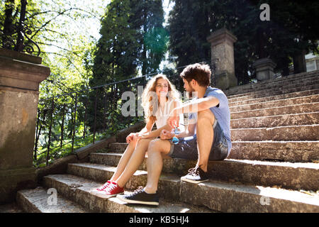 Young couple sitting on stairs in town. - Stock Photo