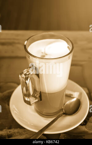 Transparent glass Cup with cappuccino coffee fat burning on the table in the cafe. Toned. - Stock Photo