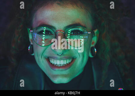 Portrait of a young woman at night illuminated with color lights - Stock Photo