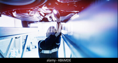 Mechanic girl watching under a car with a light in her hand - Stock Photo
