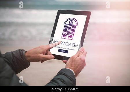 Composite image of mortgage text with icon against man using digital tablet on beach - Stock Photo