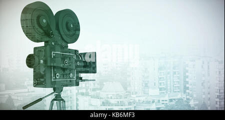 Black film reel camera with tripod against modern buildings in city - Stock Photo