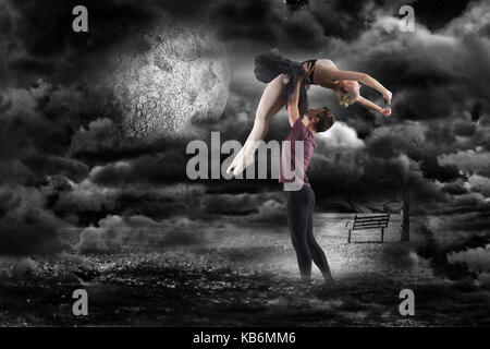Man holding ballerina  against bench in front of the moon in the night - Stock Photo