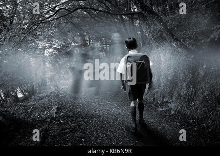 Cute pupil walking to the school bus against dark way in the woods - Stock Photo