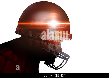 Profile view of an american football player wearing a red helmet - Stock Photo