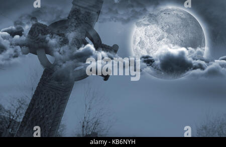 Celtic cross in front of moon behind clouds - Stock Photo