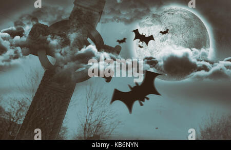 Digital image of silhouette bat against celtic cross in front of moon behind clouds - Stock Photo