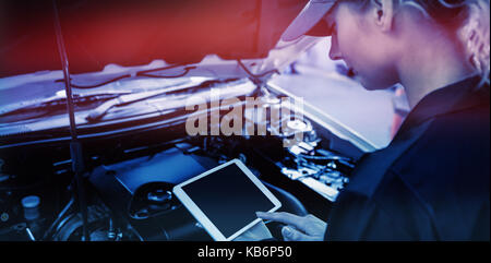 Mechanic girl using a tablet in garage in front of a car - Stock Photo