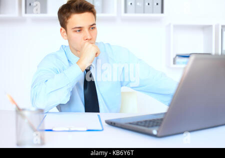 Portrait of young pensive businessman at his workplace in bright office - Stock Photo