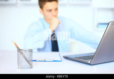 Portrait of young pensive businessman at his workplace in bright office. Focus on pencil cup - Stock Photo