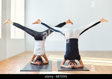 Two young women doing yoga asana open angle pose in headstand. Upavistha Konasana in Sirsasana - Stock Photo