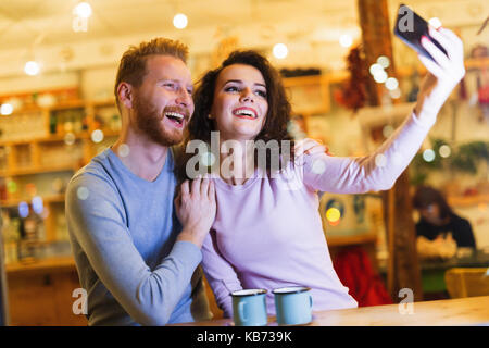 Happy couple taking selfie in coffee shop - Stock Photo