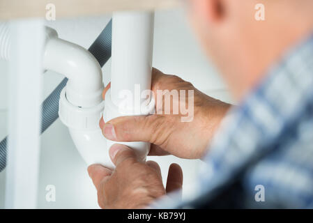 Cropped image of serviceman working on pipes under kitchen sink - Stock Photo