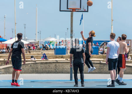 Young men playing basketball on a a sunny day on a Brighton's seafront. - Stock Photo
