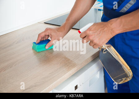 ... Midsection Of Male Janitor Cleaning Kitchen Counter With Detergent  Spray Bottle And Sponge   Stock Photo