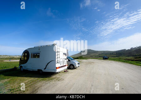 Motorhome RV and campervan are parked on a beach. Two motor home caravans are parked on a parking space for RV vehicles - Stock Photo