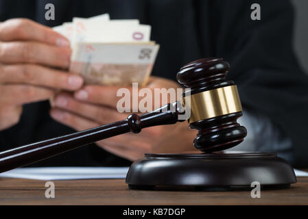 Male corrupt judge counting money at table in courtroom - Stock Photo