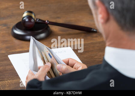 Male corrupt judge counting money in envelop at table - Stock Photo