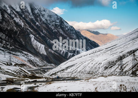 Georgian military road. The scenic winding road among the snowy mountains in Georgia. Main Caucasian Ridge and Cross - Stock Photo