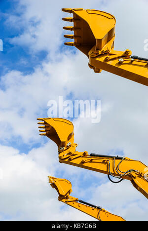 Buckets of three digger excavators against a blue sky - Stock Photo