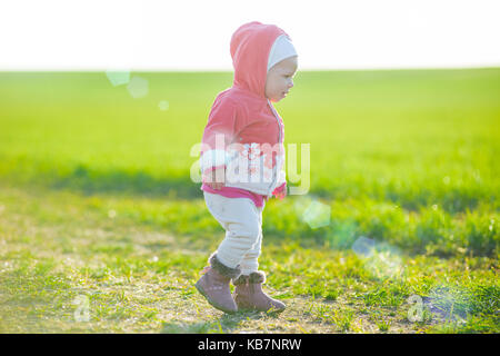 Happy little girl walking in the meadow and looking at sun - Stock Photo
