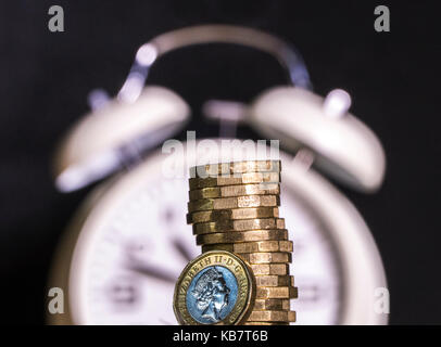 Defocused alarm clock with new pound coins. Concept of link between  timescale and British money / UK pounds sterling, - Stock Photo