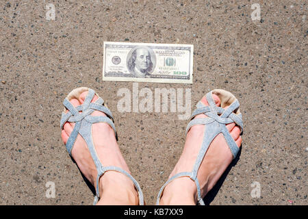 Lucky woman finding money on the street. Women feet next to hundred dollar bill. Lost and found money lying down - Stock Photo