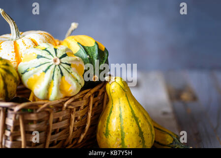 Closeup of decorative gourds and pumpkins in a basket on natural rustic wooden background - Stock Photo
