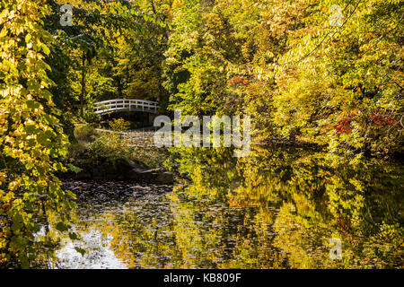 A white bridge crossing a lake at Montreal's Jean-Drapeau Park, in early   fall. - Stock Photo