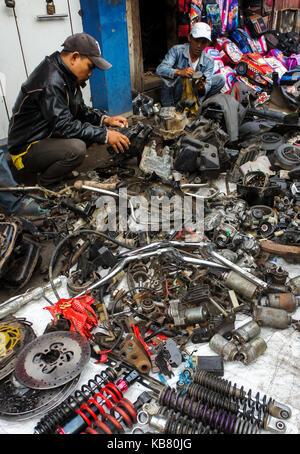 Street vendor sells used spareparts at morning market, Palembang City, South Sumatera, Indonesia - Stock Photo