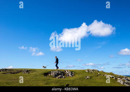 Man walking with his dog near Eoropie Beach, Isle of Lewis in the parish of Ness, in the Outer Hebrides, Scotland - Stock Photo
