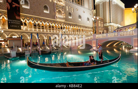 A couple enjoy a ride in a gondola that is offered by The Venetian Hotel in Las Vegas, Nevada. - Stock Photo