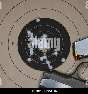 Results of target practice and a small pistol with magazine. - Stock Photo