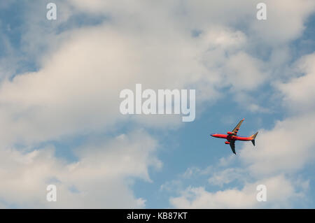 Jet aircraft flying through the clouds in the sky - Stock Photo