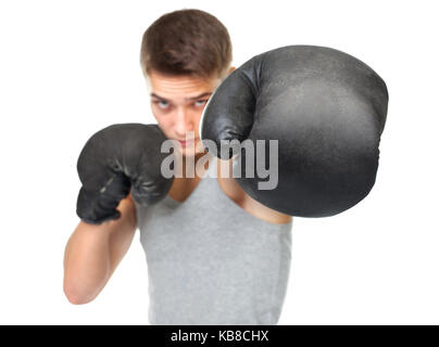 Portrait of young boxer throwing a punch at the camera isolated on white background. Focus on boxing glove - Stock Photo