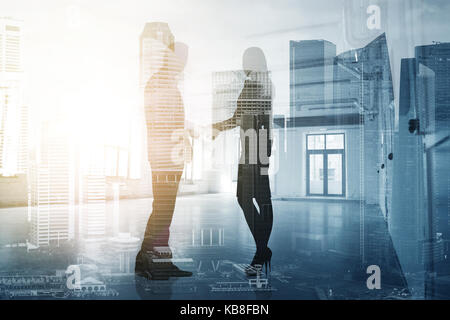 business people shaking hands over city background - Stock Photo