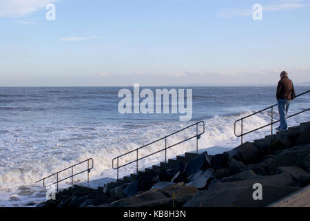 Person on Steps Leading Down To The Beach as the Tide Comes In At Seaton Carew Hartlepool - Stock Photo