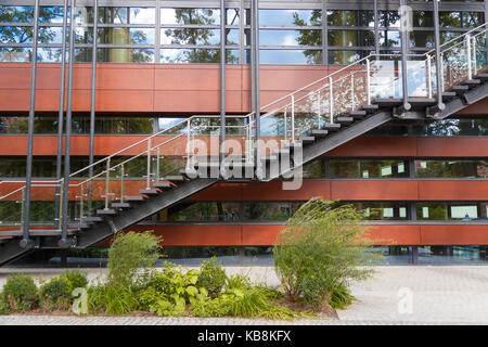 Fire escape staircase emergency exit on the background of the modern building facade. - Stock Photo